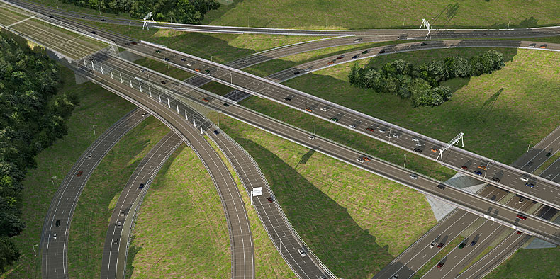 A birds-eye view of multiple connected highways and cars surrounded by green grass and trees