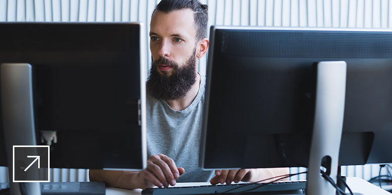 A man working on two monitor screens
