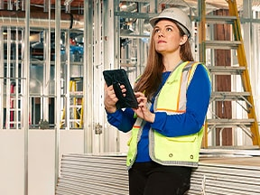 Eine Frau auf einer Baustelle greift auf einem Tablet auf ihre DWG-Dateien zu