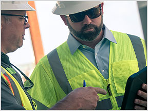 Dos hombres en un emplazamiento de construcción ven dibujos en una tableta mediante la aplicación AutoCAD móvil.