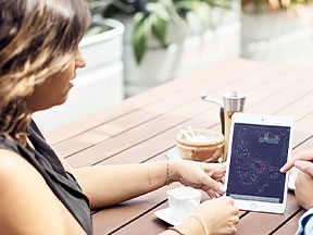 Dos personas en una mesa, colaborando y realizando cambios de diseño en una tableta.