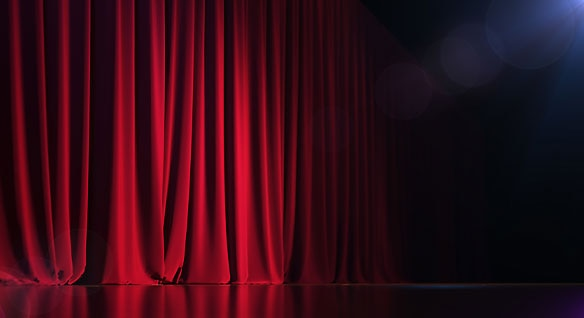 A theater stage with red velvet curtain