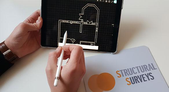 Un géomètre dessine une conception sur une tablette avec l'application mobile AutoCAD