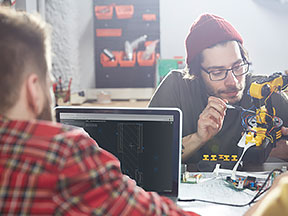 Three people working on a design prototype and using a laptop computer