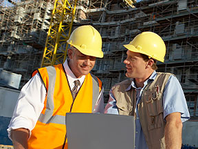 Two men in hard hats look at laptop computer on a building site