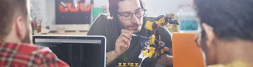 Tres personas trabajando en un prototipo de diseño y utilizando una computadora portátil.