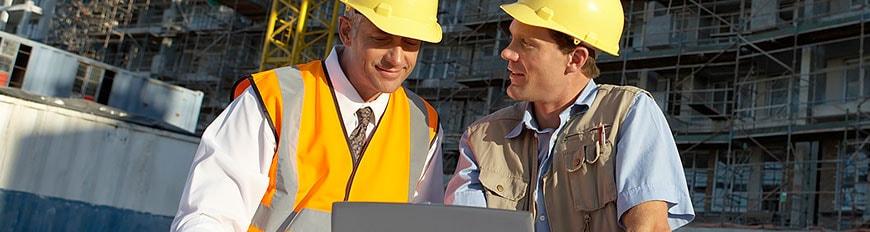 建設現場でノートパソコンの画面を見ているヘルメット着用の 2 人の男性
