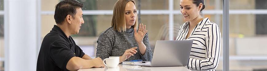 テーブルに向かい、ノートパソコンの画面を見ている 3人のユーザー