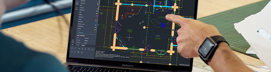 Two people sitting at a desk using AutoCAD web app on laptop