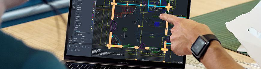 デスクに向かい、ノートパソコンで AutoCAD Web アプリを使用している 2 人のユーザー