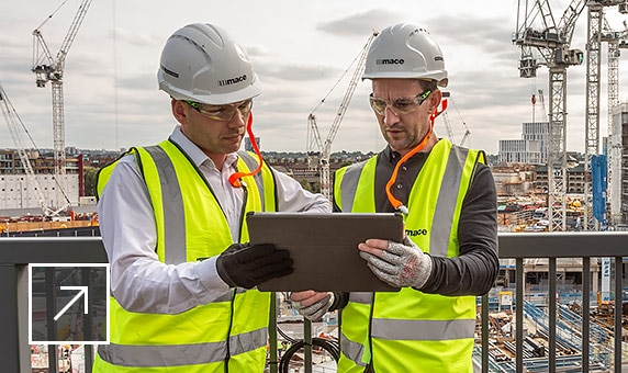 Two men on a construction site sharing a tablet