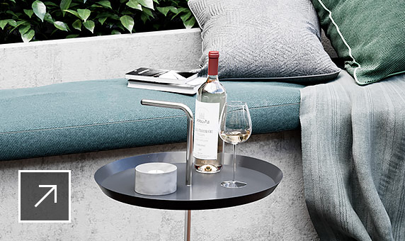 Detailed rendering of outdoor patio, surrounding greenery, wood floor, a stone bench with textured cushions and a table with wine bottle and glass