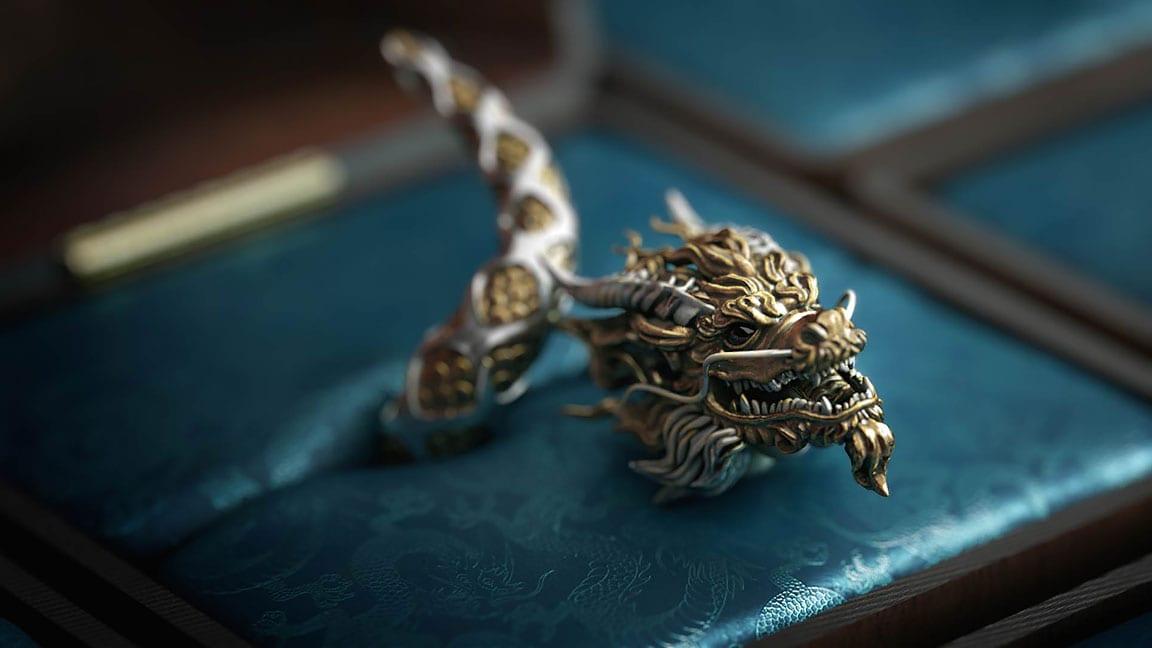 Anel de ouro e prata com uma forma intricada de dragão numa caixa de anel forrada a brocado azul