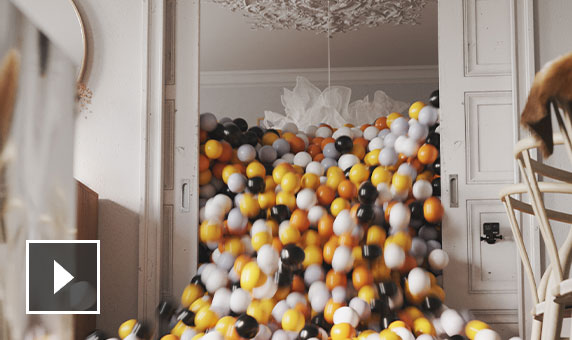 Video: silent animation of empty indoor space where a door suddenly opens to let out an avalanche of many-coloured balls