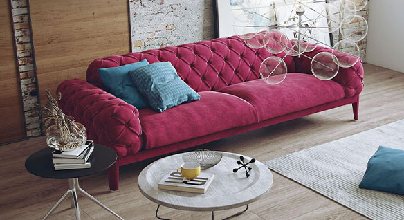 Rendering of modern living space dominated by plush, berry-coloured velvet Chesterfield sofa