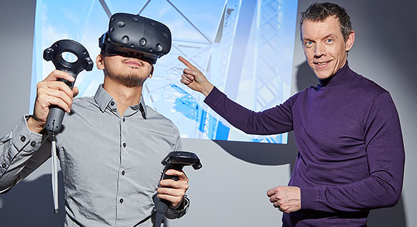 LiRo's director of virtual design points to a man trying out their virtual reality headset and remote controls