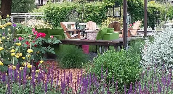 Jardín de flores frondoso y plataforma con muebles de jardín