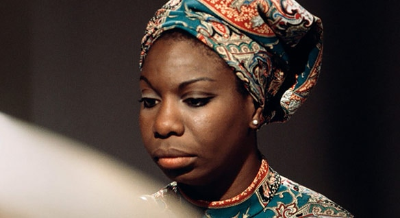 Close-up of the face of a young Nina Simone, eyes downcast and wearing a brightly patterned head scarf