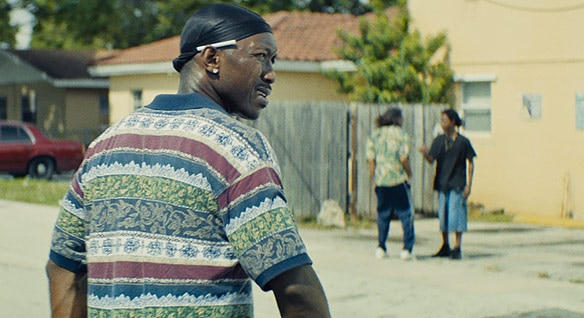 Scene in Moonlight where Mahershala Ali looks back as he walks away from the camera with 2 young men in the background