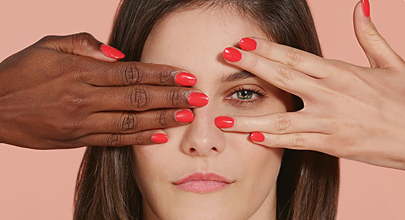An African American hand and a Caucasian hand with red fingernails partially covering a young Caucasian woman's face