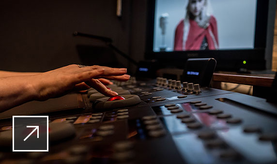 A person touching a track ball on a video editing console