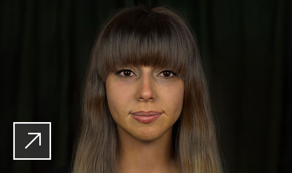 Photo of the face of a young woman who's half-smiling, with brown eyes and brown hair with fringe