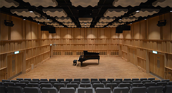 Performance space rendering with seats facing an open area with a concert piano, and soundproofing materials on the walls and ceiling