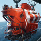 Red submarine suspended with ropes and pulleys over the ocean