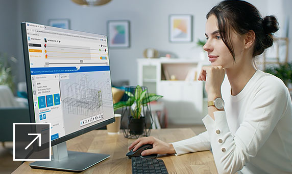 Woman sitting at a desk viewing her computer screen while using BIM Collaborate software.