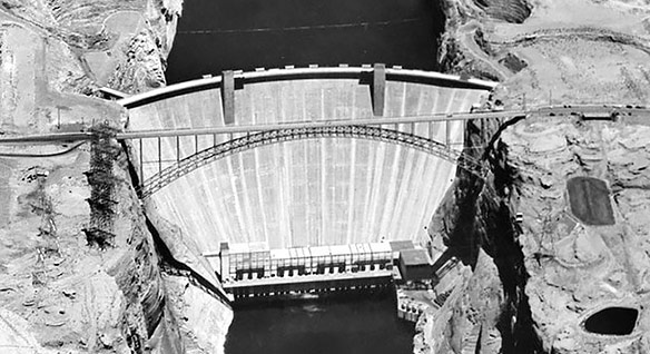 Black-and-white aerial view of a concrete dam set in a rock canyon