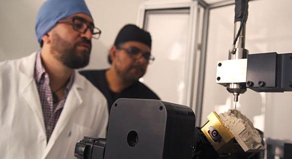 Zwei Männer prüfen, wie eine Maschine ein Schädelimplantat fertigt