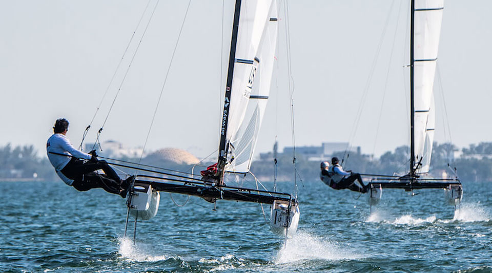 US Sailing team members sailing on the water on 2 hydrofoiling dinghies