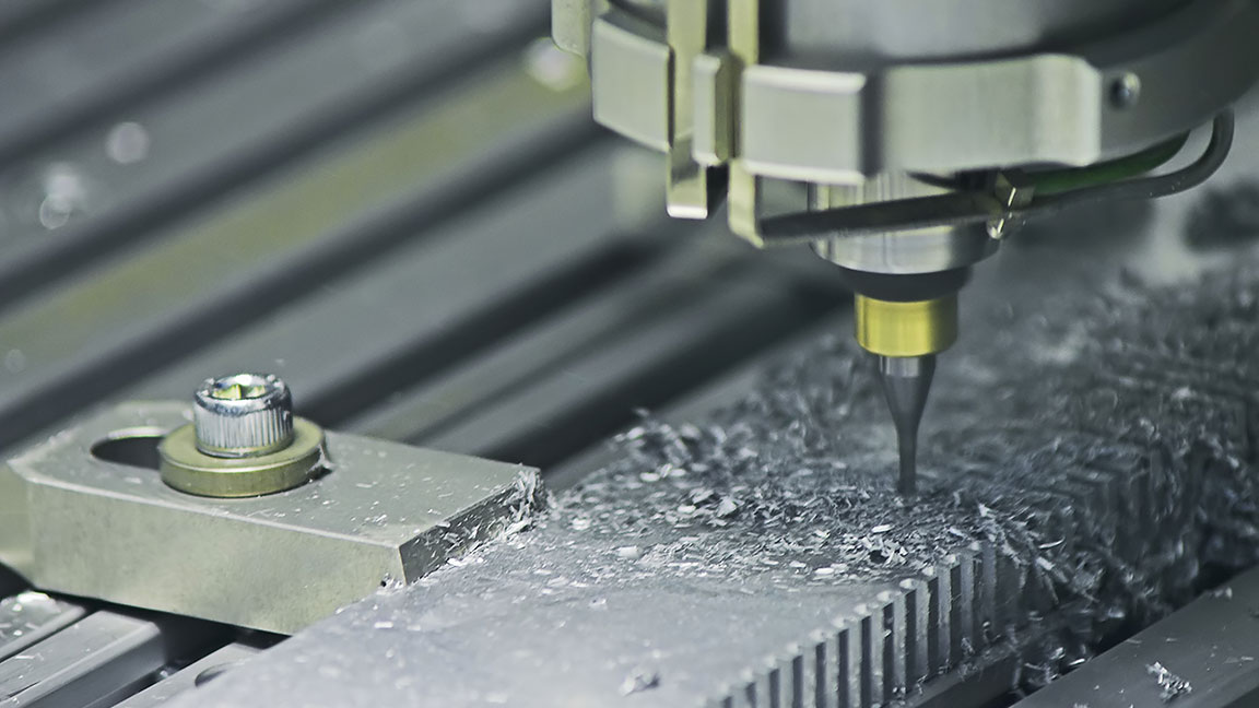 Close-up view of the fabrication of a metal part with a drill bit