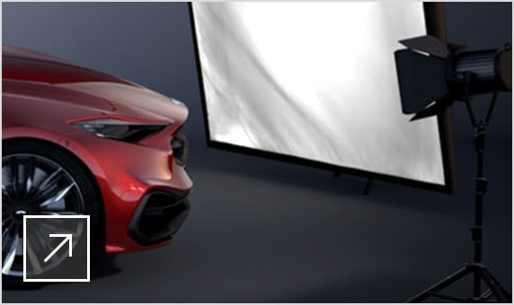 VRED scene of a red sports car on a set with camera lights and a large reflector lighting up the car