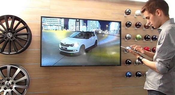 壁に取り付けられた大型モニターの前でタブレットを持っている男性と、画面に表示された白の自動車と背景のビル群