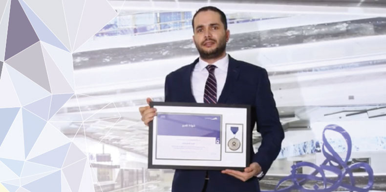 Portrait of Wajdi holding award