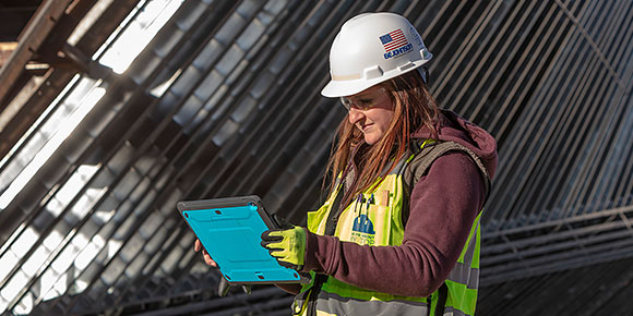 A woman wearing safety gear working on a construction site and using a tablet