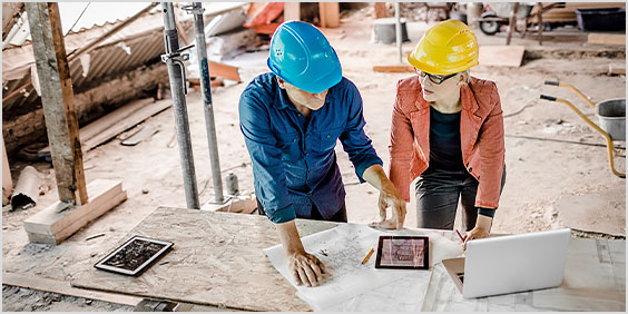 Two construction workers viewing architectural designs on a tablet at a construction site