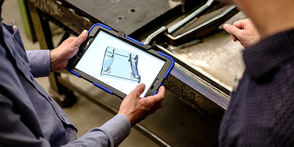Engineers accessing manufacturing data on tablet, showing automated workflows