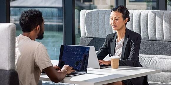 在 Autodesk 旧金山技术中心,两个人坐在一个展位上用电脑一起工作。