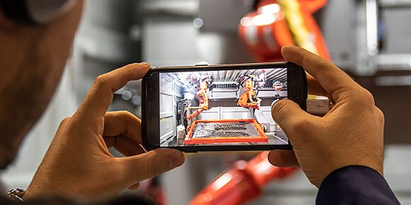 参会者在 Autodesk University 的博览会厅拍摄技术展览的照片