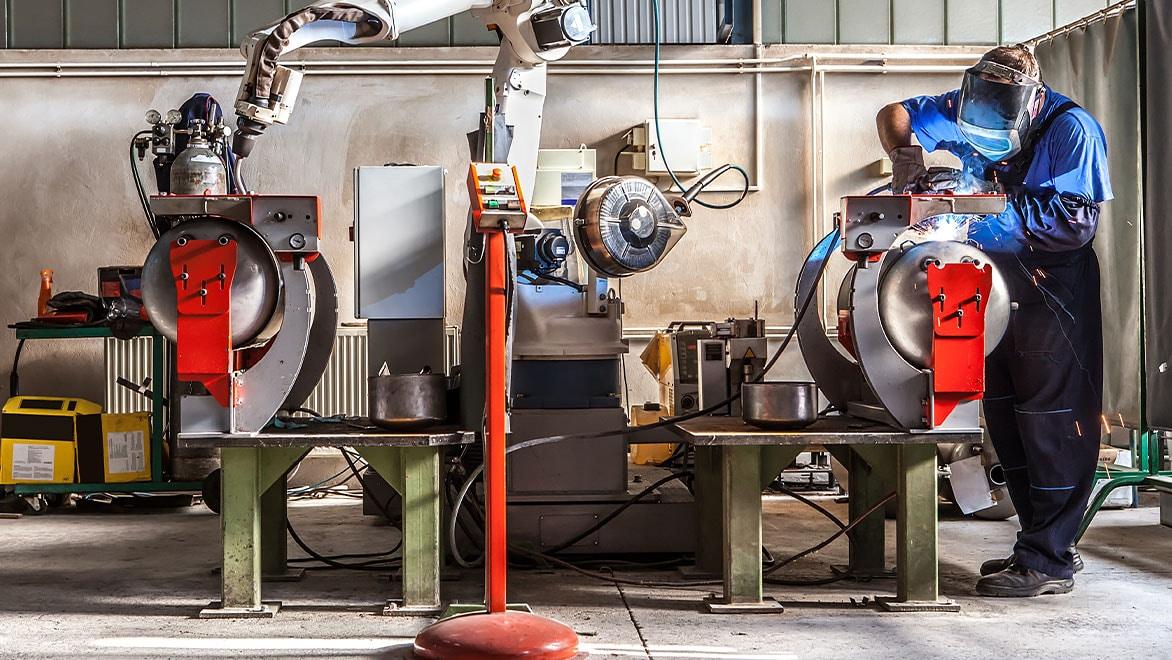 一名男子在机器人实验室戴着面罩进行焊接。
