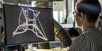一名男子在电脑前查看设计并冥思苦想。