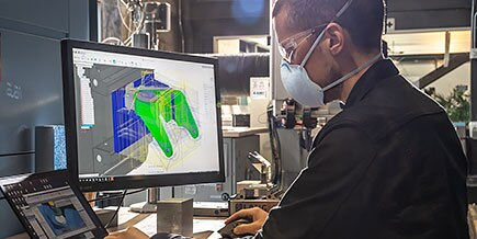 一名男子在笔记本电脑上使用 Fusion 360,在 Autodesk 旧金山技术中心设计铣削项目。