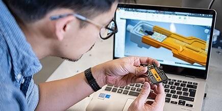 Autodesk 技术中心的一名男子在笔记本电脑上检查橙色和黑色的电脑芯片。