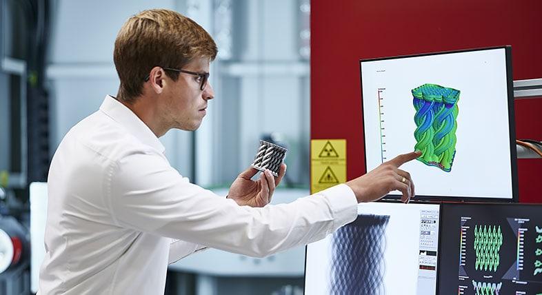 一名男子在技术中心工作,他一只手拿着产品模型,并将其与计算机屏幕上的数字模型进行比较。