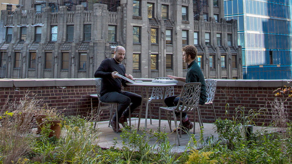 2 men sitting on rooftop terrace, surrounded by buildings in New York City