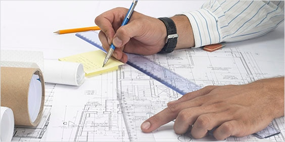 Close-up view of an architect working on blueprints.