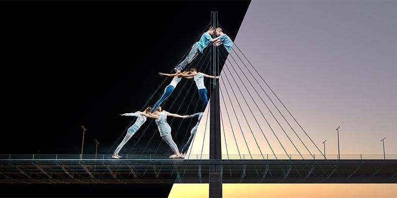 Acrobats balancing on a truss