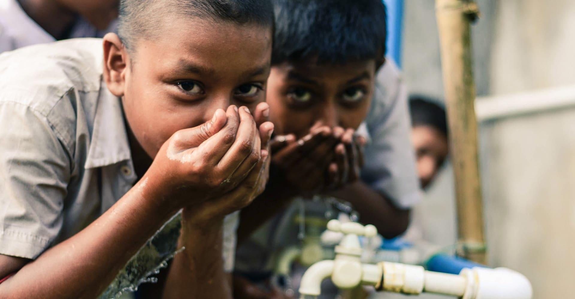Niños beben agua limpia
